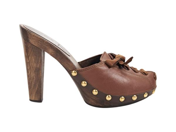 c185d94051e1 Product details  Brown leather heeled mules by Miu Miu. Accented with  studs. Lace-up front panel. Round toe. Wooden heel and platform. Slip-on  style.
